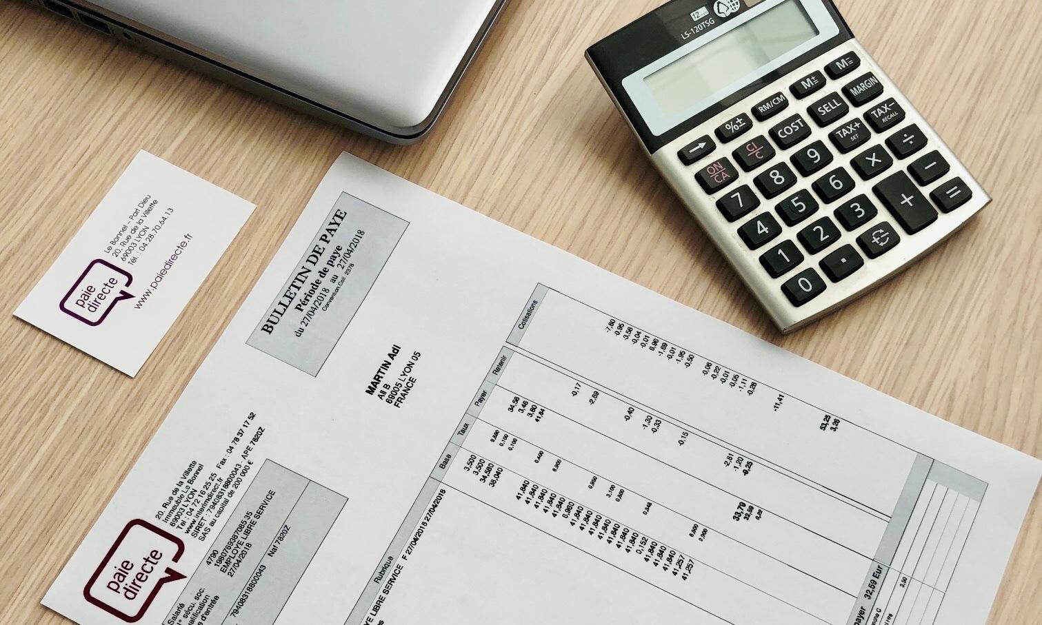 Exemple de fiche de paie réalisée par Paie Directe, posée sur un bureau à côté d'une carte de visite Paie Directe, d'une calculatrice et un ordinateur